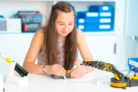 Teen girl in robotics laboratory,  school class