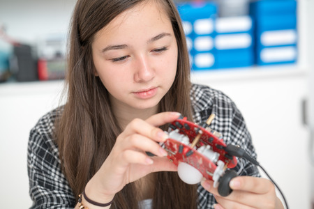 girl in robotics class research electronic device