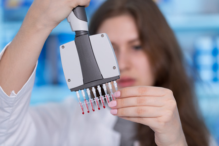 Young woman in biological laboratory. Attractive young female scientis.Young scientist pipetting with multi pipette in genetic lab. Stock Photo