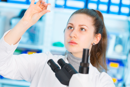 Young woman in biological laboratory. Attractive young female scientis. Girl with a slide for the microscope University Hospital