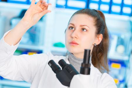 Mujer joven en laboratorio biológico. Hembra joven atractiva Scientis. Chica con una diapositiva para el microscopio Hospital Universitario