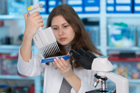 science tips: Young woman in biological laboratory. Attractive young female scientis.Young scientist pipetting with multi pipette in genetic lab. Stock Photo
