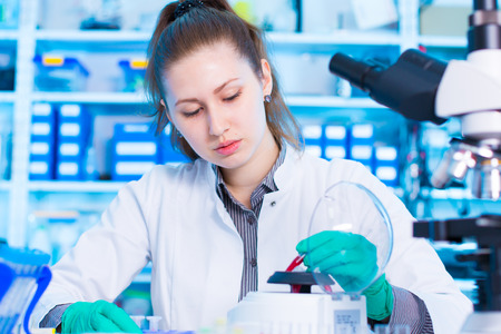 centrifuge: woman in a laboratory with microtube test tube in hand and PCR centrifuge. scientist using a centrifuge in a laboratory