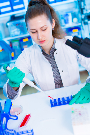 pcr: A young chemist holding test tube with liquid during chemical experiment.  Assistant in laboratory with pipette research of cancer stem cells.  Female medical or scientific researcher using test-tube on laboratory. Woman cientist concentrates to load stri Stock Photo