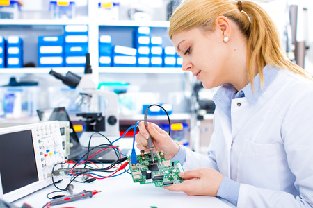 Engineer working with circuits. A woman engineer solders circuits sitting at a table. Microchip production factory. Technological process. Assembling the PCB board. Girl repairing electronic device on the circuit board.  Foto de archivo