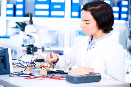 Engineer working with circuits. A woman engineer solders circuits sitting at a table.  Microchip production factory. Technological process. Assembling the PCB board.  Girl repairing electronic device on the circuit board.
