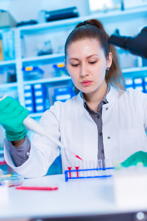 concentrates: A young chemist holding test tube with liquid during chemical experiment.  Assistant in laboratory with pipette research of cancer stem cells.  Female medical or scientific researcher using test-tube on laboratory. Woman cientist concentrates to load stri Stock Photo