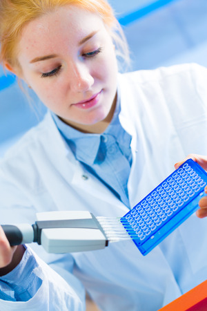 Young women use laboratory dispenser or pipette  in microbiological or medical laboratory