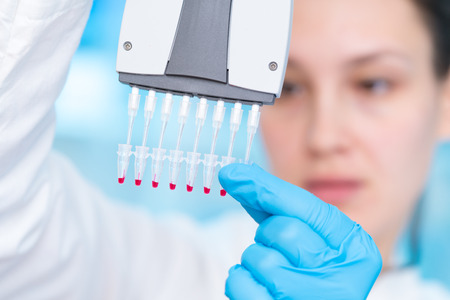 Woman technician with multipipette in genetic laboratory PCR research. Student girl use pipette. Young female scientist loads samples for DNA amplification by PCR Stock Photo