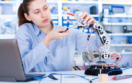 Girl in robotics laboratory. Young woman technician repair roboter manipulator 스톡 콘텐츠