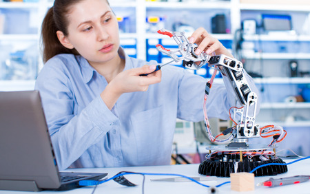Girl in robotics laboratory. Young woman technician repair roboter manipulator Stock Photo