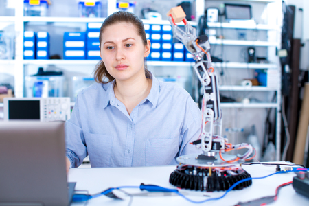 manipulator: Girl in robotics laboratory. Young woman technician repair roboter manipulator Stock Photo