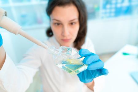 Vrouw technicus met multipipette in genetisch laboratorium PCR onderzoek. Student girl gebruik pipet. Jonge vrouwelijke wetenschapper laadt steekproeven voor DNA-amplificatie door PCR