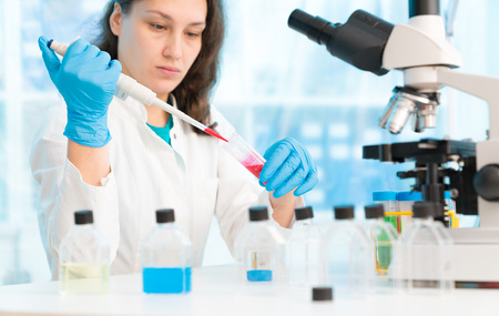 pcr: Woman technician with multipipette in genetic laboratory PCR research. Student girl use pipette. Young female scientist loads samples for DNA amplification by PCR