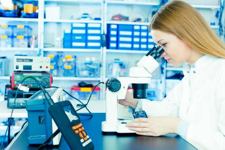 woman engineer: woman with microscope in microelectronics laboratory
