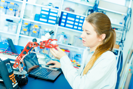 Young woman worked with robot arm