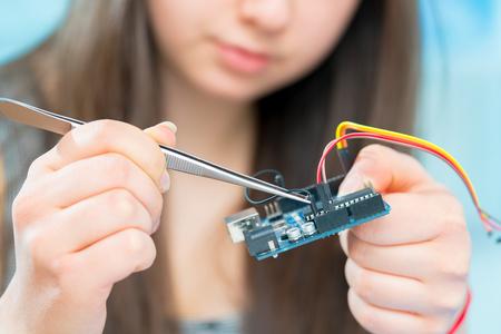 Student meisje in elektronica laboratorium, experiment met microcontroller en robot cnc module Stockfoto - 76412320