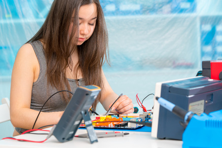 componentes: chica estudiante en laboratorio de electrónica, experimentar con microcontrolador y CNC robot módulo