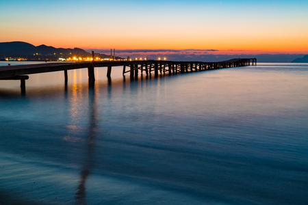 Sunset on a sandy beach and a wooden pier, Panorama Stock Photo