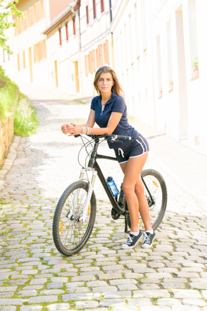 Young brunette woman in shorts riding a sport bike in a sity Stock Photo