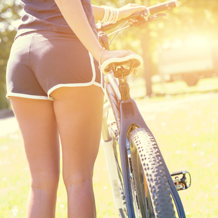 Young woman in shorts riding a sportbike in a spring park