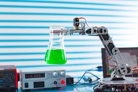 Robot in chemical industry. Roboter arm take test tube with dangerous fluid