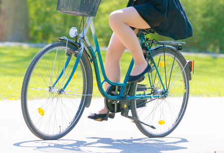 Girl on bicycle wearing on black short dress. Young Woman riding along road on green spring  outdoor Park. Sporty young girl riding a bicycle on a sunny morning