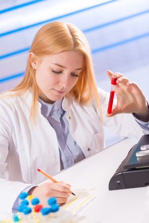 hematology: Female laboratory assistant with blood test for AIDS Stock Photo