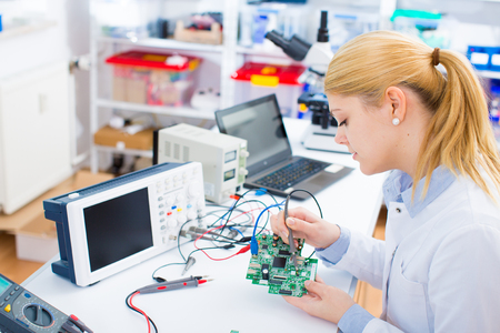 Female laboratory assistant Repairs PCB module for CNC robotics. Measurement of the parameters of the electronic system in the laboratory Archivio Fotografico