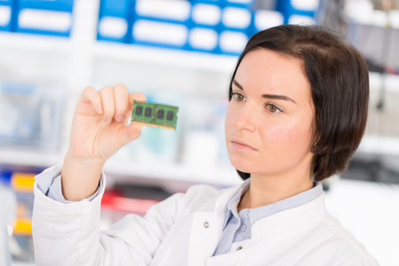 to mend: Female laboratory assistant Repairs PCB module for CNC robotics. Measurement of the parameters of the electronic system in the laboratory Stock Photo