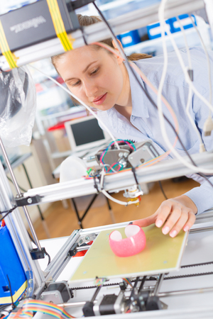 A female student or laboratory assistant in the automation laboratory is debugging the work of the 3d printer. 3d printer is a device for modeling 3D objects Stock Photo