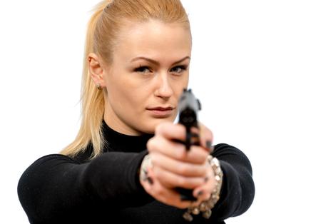 Jonge blonde vrouw in een zwart pak met een pistool