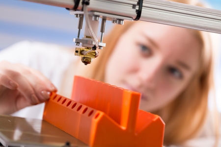 A female student or laboratory assistant in the automation laboratory is debugging the work of the 3d printer. 3d printer is a device for modeling 3D objects 写真素材