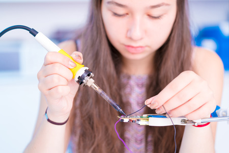 Schoolgirl in electronics class uses a soldering iron 스톡 콘텐츠