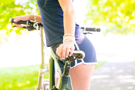 long: Young slim woman standing next to bicycle Stock Photo