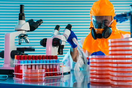 contagious: Research Of dangerous viruses in the laboratory. Prevention of a pandemic. A scientist in a biological protective suit works with a pipette