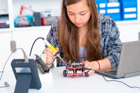 Schoolgirl in the school robotics laboratory with a robot model Banque d'images