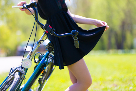 Girl next to a bicycle holds a skirt edge of a short black dress, Summer park Stock Photo