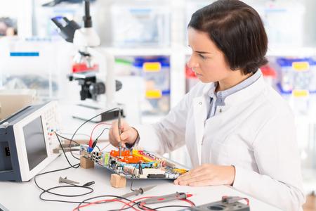 Assistant de laboratoire féminin Réparation du module PCB pour la robotique CNC. Mesure des paramètres du système électronique en laboratoire