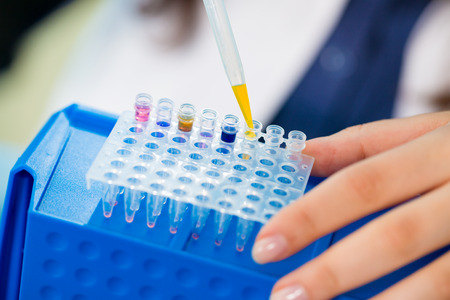 pcr: Young female technician in genetic laboratory with PCR