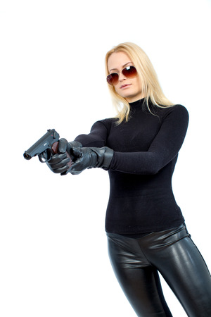 Young blonde woman in a black suit with a gun Imagens - 85938387