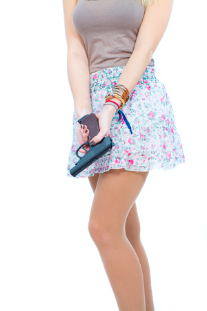 Blonde young woman in short skirt with gun on white background