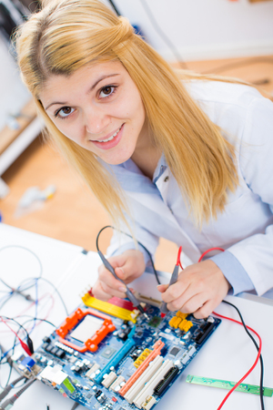 parameters: Female laboratory assistant Repairs PCB module for CNC robotics. Measurement of the parameters of the electronic system in the laboratory Stock Photo