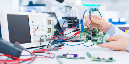 Female laboratory assistant Repairs PCB module for CNC robotics. Measurement of the parameters of the electronic system in the laboratory Editorial
