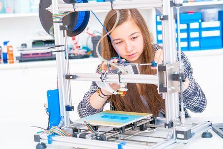 Schoolgirl prints 3d model from plastic on 3d printer 写真素材