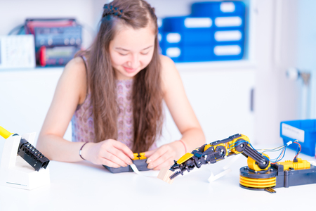 girl is experimenting with a robot Stock Photo