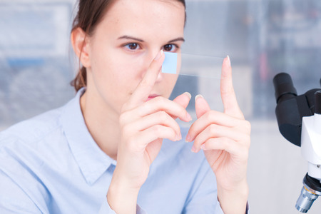Biopsia: student girl with glass empty microscope slide in hand