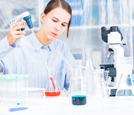 adding: Woman Scientist Adding Liquid To Test Tube With Pipette In Lab