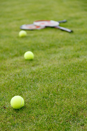 Racket and balls for tennis on green grass