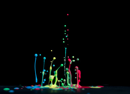 Jumping drops of paint or ink on a black background. multi-colored abstract shapes. Color splash